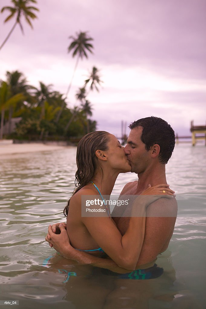 a caucasian couple embrace and kiss in the water as they relax in a tropical locale : Foto de stock