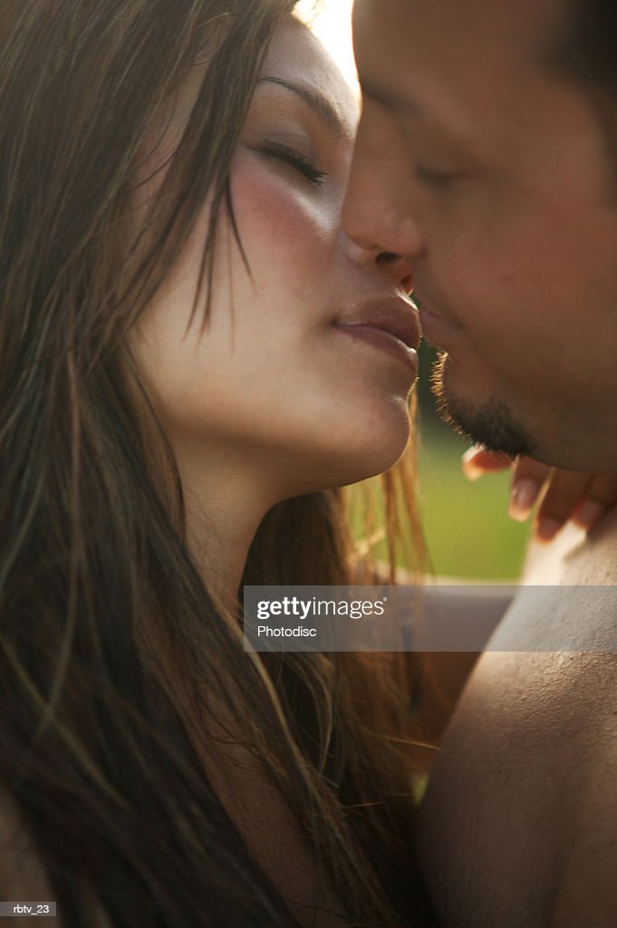 a caucasian couple embrace and kiss on a beach as they vacation in the tropics : Foto de stock