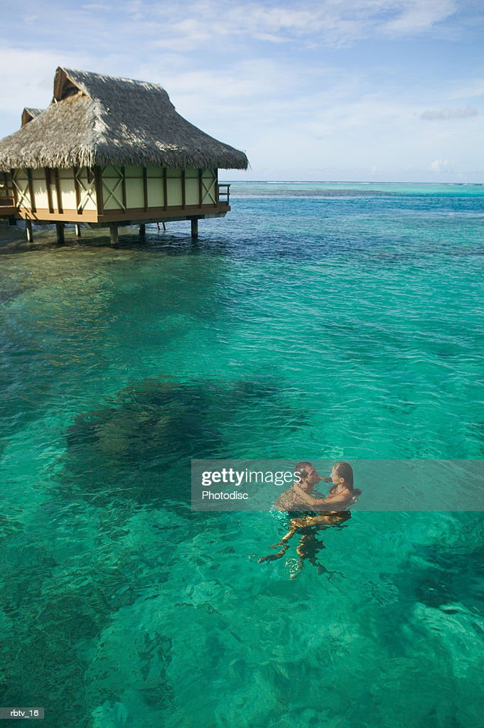 a caucasian couple embrace and swim through the clear water at a tropical resort : Foto de stock