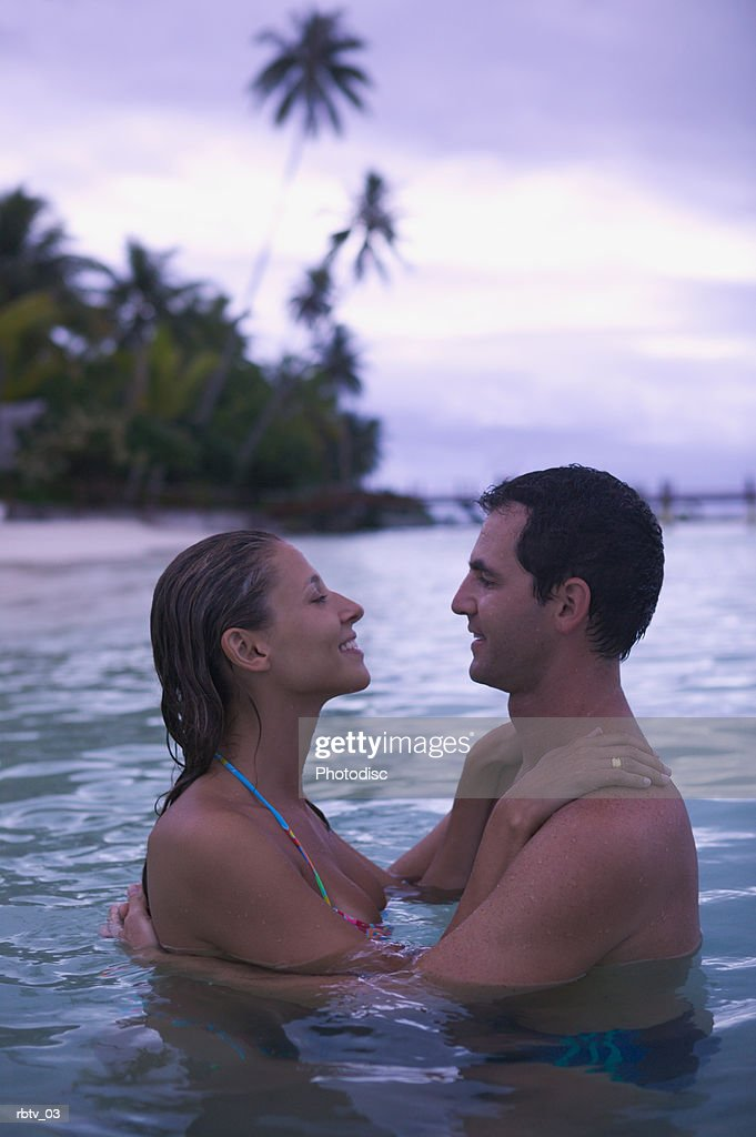 a caucasian couple embrace in the water as they relax in a tropical locale : Foto de stock