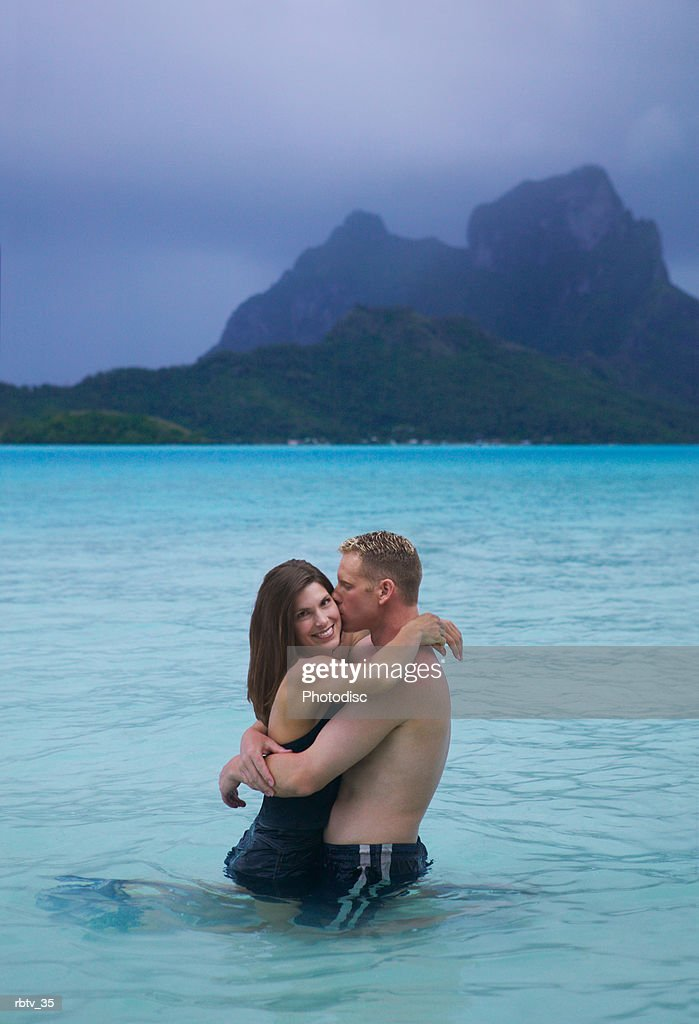 a caucasian couple embrace in the water as they vacation at the beach : Stockfoto