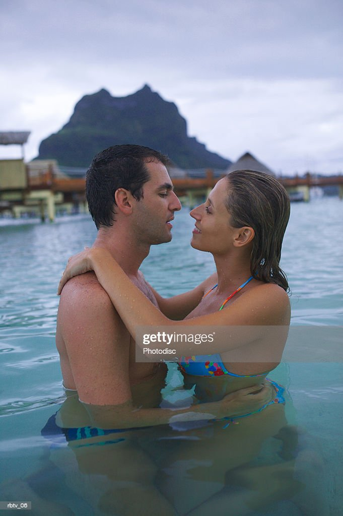 a caucasian couple embrace in the water as they vacation in a tropical resort : Foto de stock