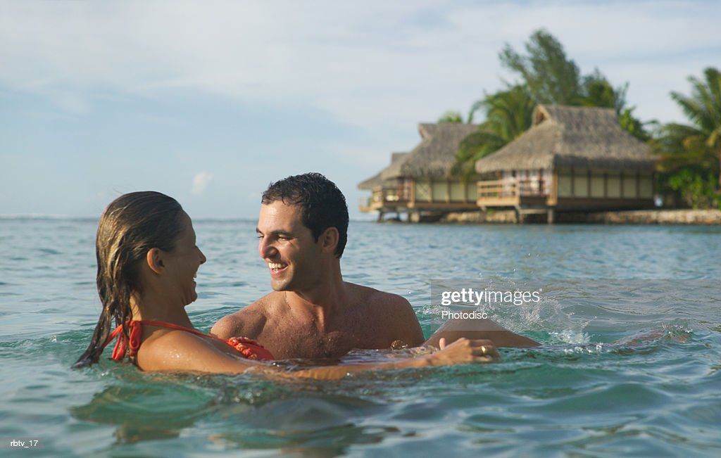 a caucasian couple embrace in water at a tropical resort : Foto de stock