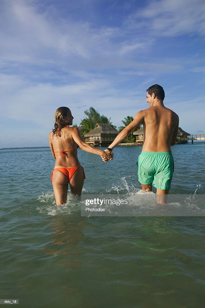 a caucasian couple hold hands and run through the water as they vacation in a tropical setting : Foto de stock