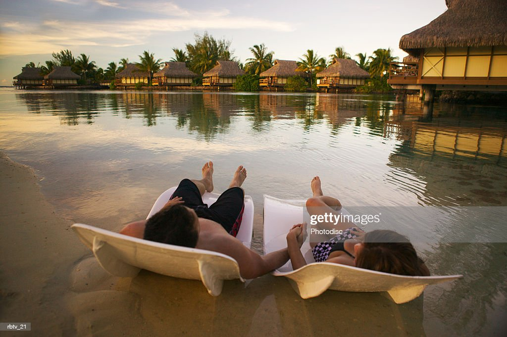 a caucasian couple hold hands relaxing on beach chairs as they vacation in a tropical setting : Foto de stock