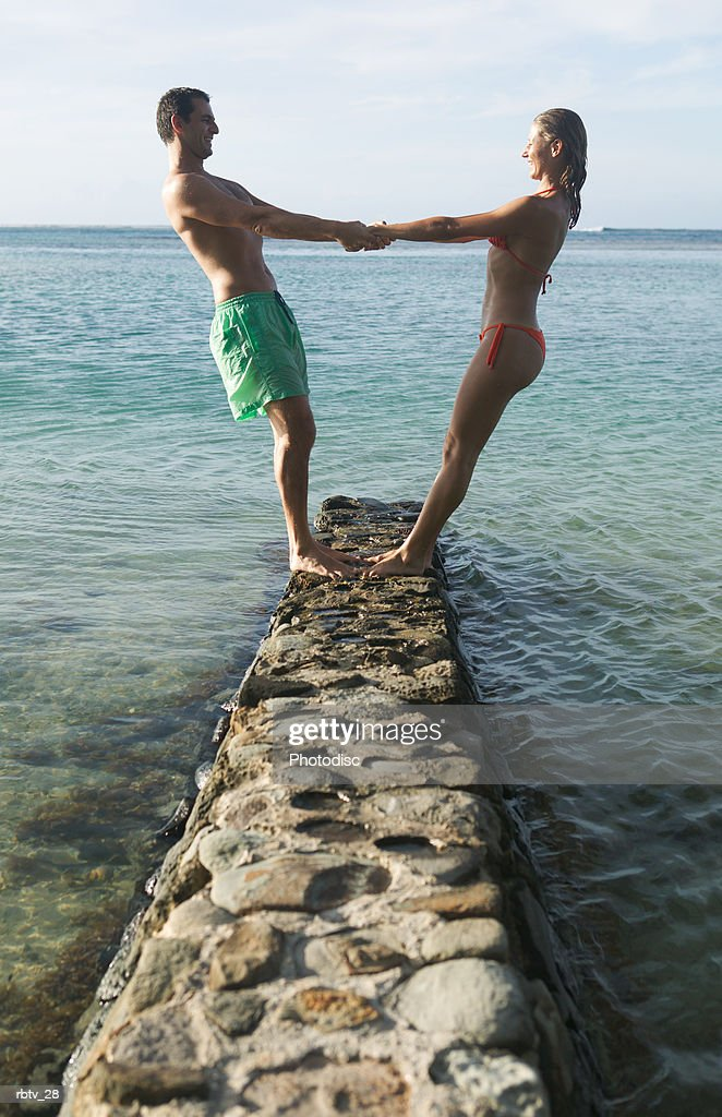 a caucasian couple in swimsuits holds hands and lean back white playing on a stone bridge at the beach : Foto de stock