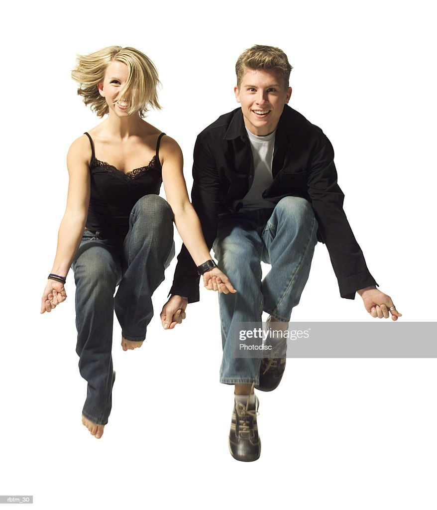 a caucasian couple jump up together and playfully snap their fingers : Foto de stock