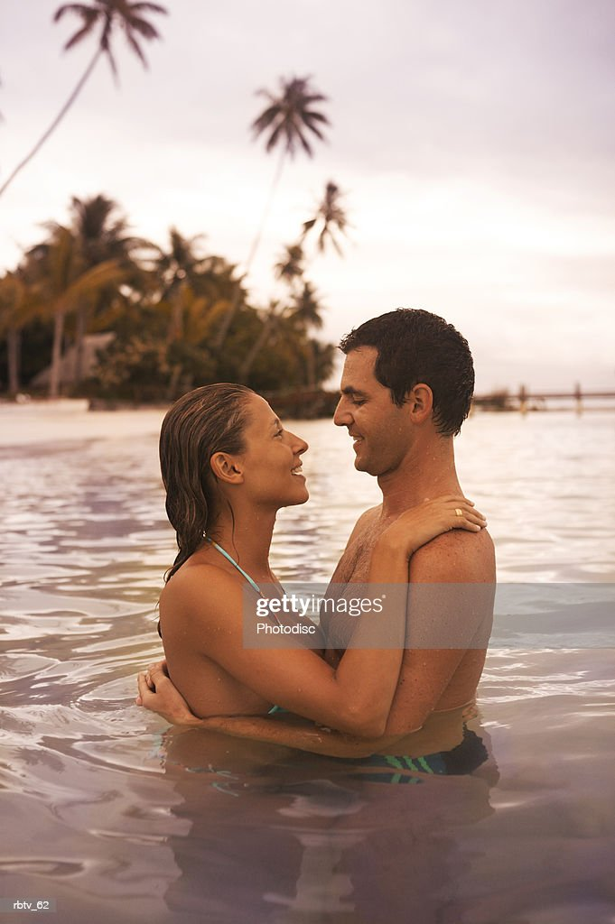 a caucasian couple lovingly embrace each other in the water while vacationing in the tropics : Foto de stock