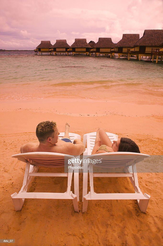 a caucasian couple sit in beach chairs as they overlook a beautiful beach resort in the tropics : Stockfoto
