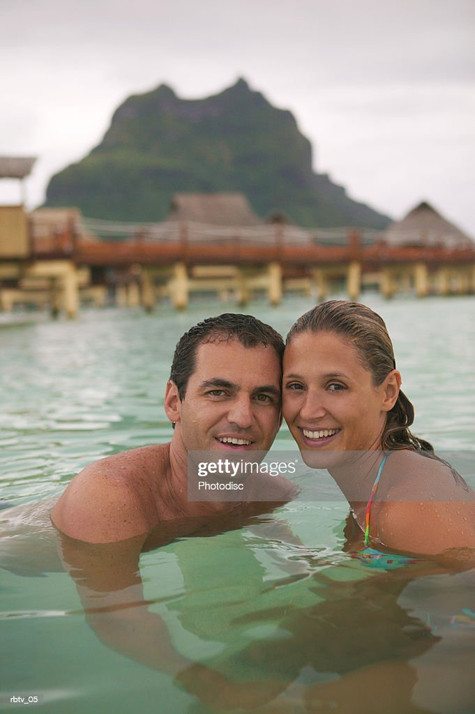 a caucasian couple smile at the camera as they swim in the water at a tropical resort : Foto de stock