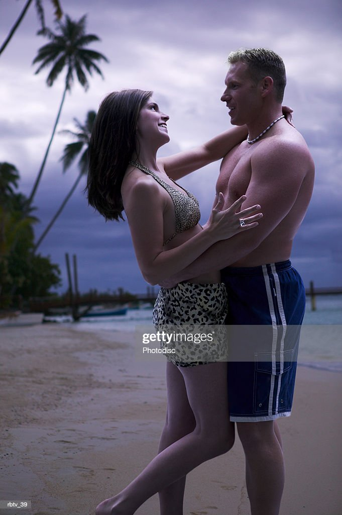 a caucasian couple stand on a beach at sunset as they hug and smile : Foto de stock