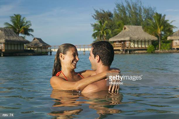 a caucasian couple swim and hug in the water while vacationing at a tropical resort
