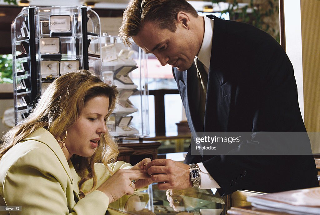 a caucasian customer shops for rings at a jewelry store : Foto de stock