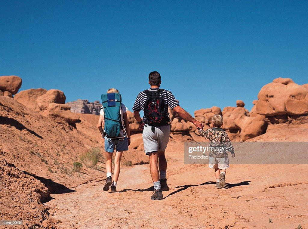 a caucasian family walks away on a family hike through redrock desert : Stockfoto