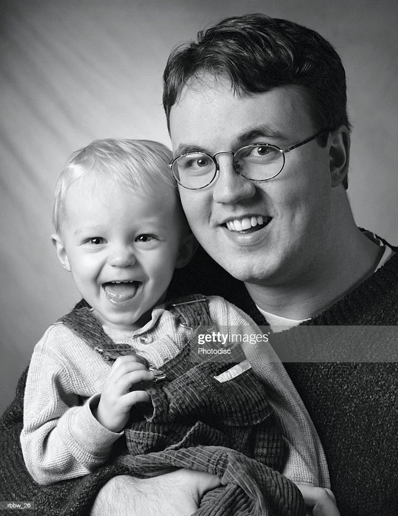 a caucasian father holds his young son while laughing and smiling into the camera : Stockfoto