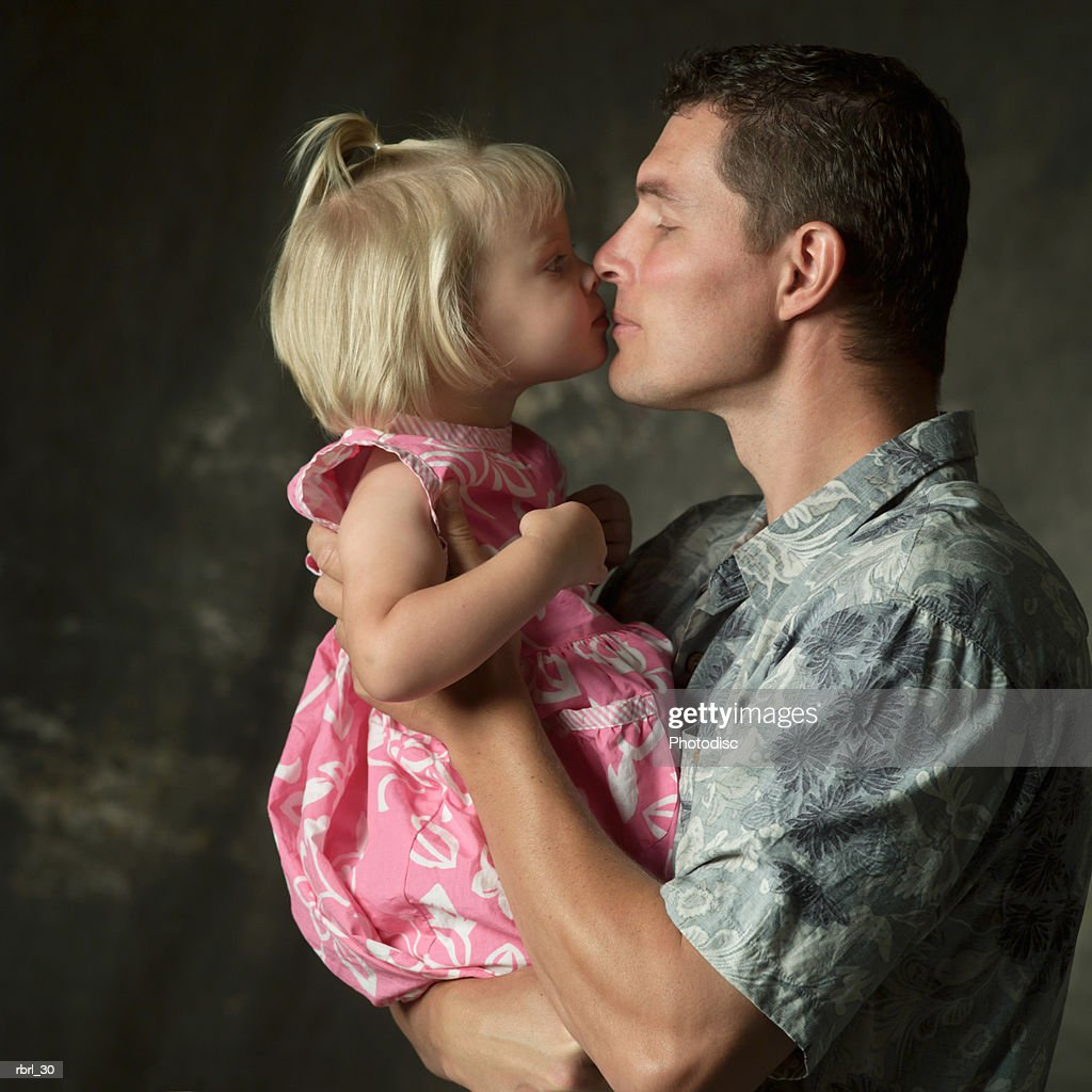 a caucasian father holds up and gives a kiss to his young daughter : Foto de stock