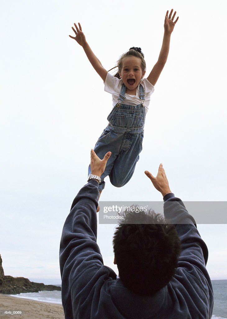 a caucasian father tosses his laughing daughter in the air at the beach : Stockfoto