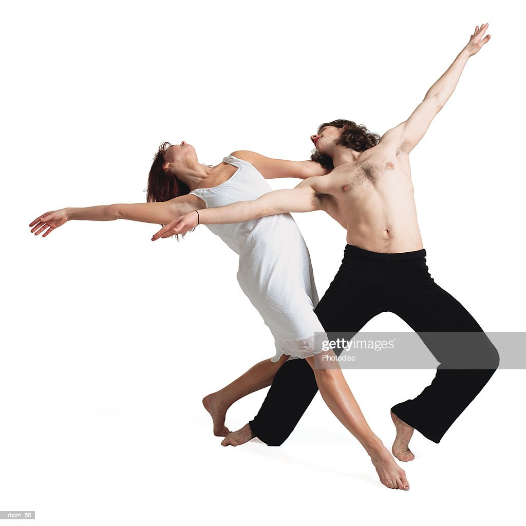 a caucasian female in a white dress leans back and outstretches her arm in a ballet type dance with her shirtless male partner : Foto de stock