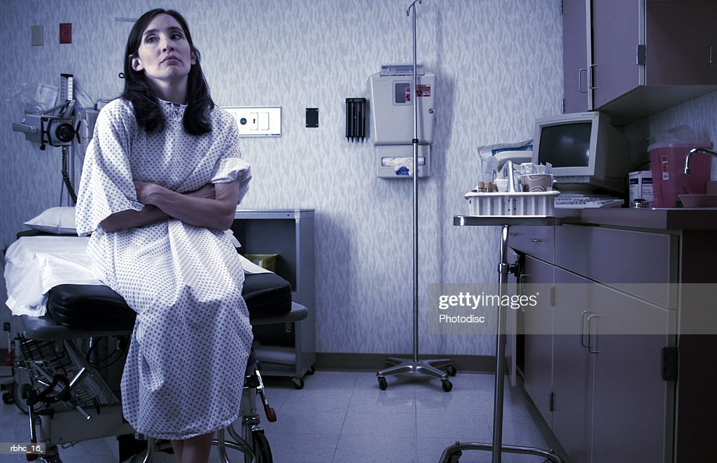 a caucasian female patient in a hospital gown sits in an exam room and waits : Stock Photo