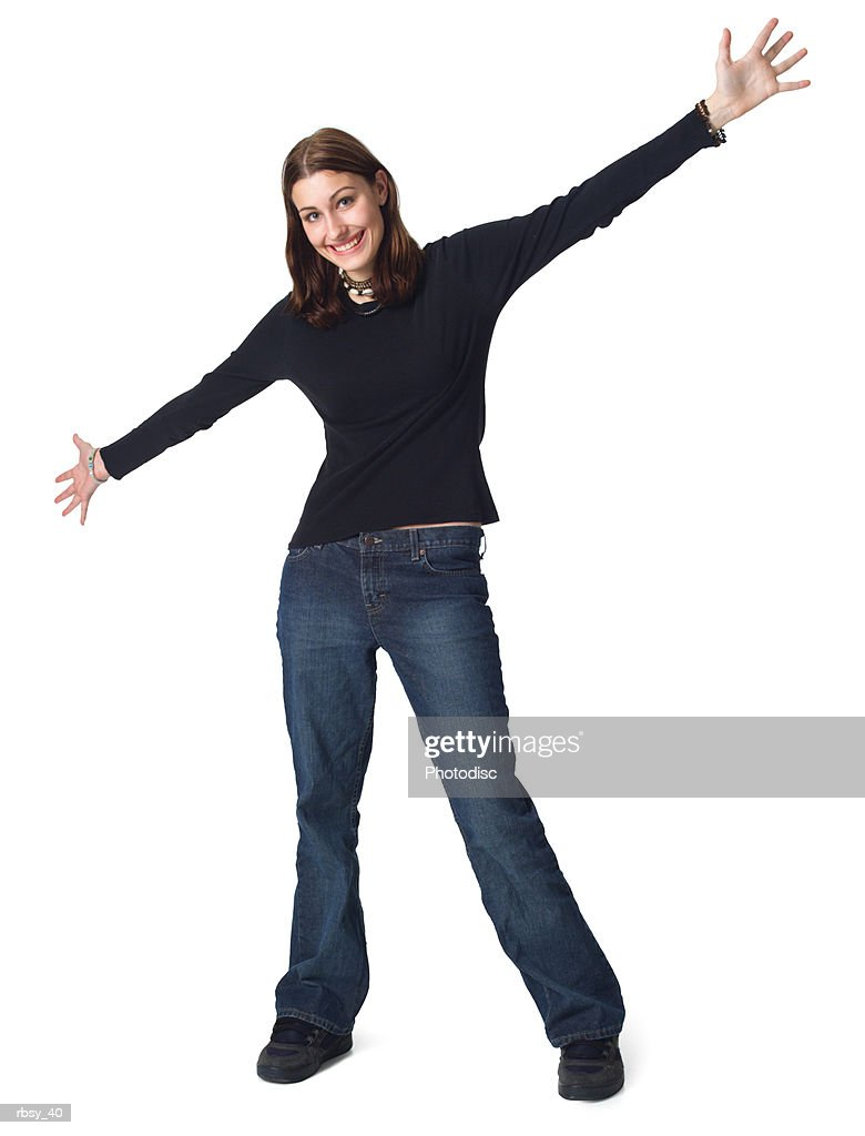 a caucasian female teen in jeans and a black shirt stretches out her arms and smiles : Foto de stock