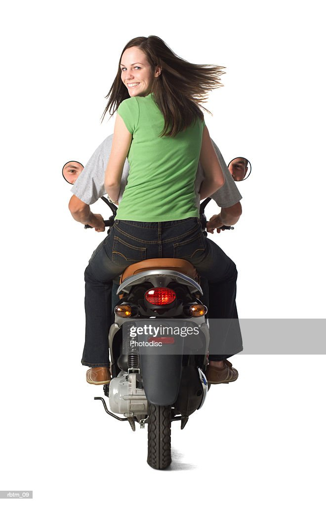 a caucasian female teen in jeans and a green shirt smiles as she rides with her boyfriend on a scooter : Foto de stock