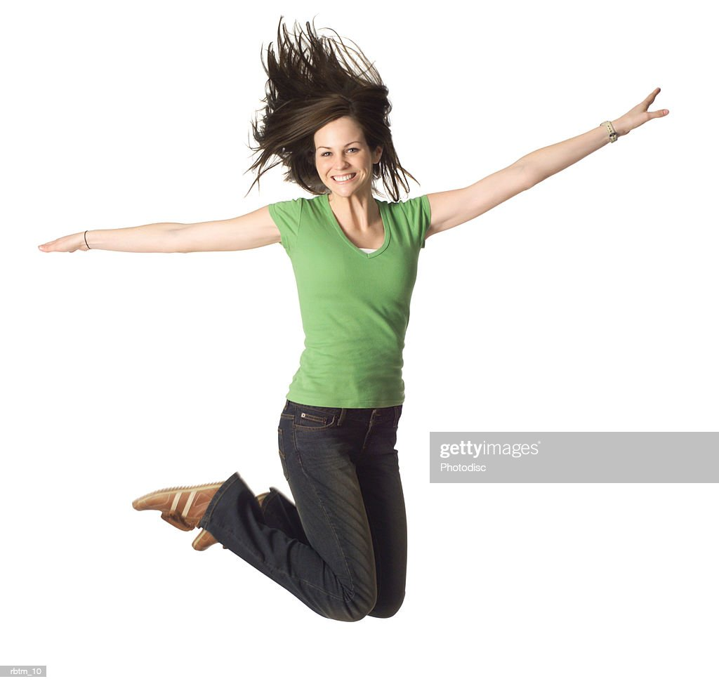 a caucasian female teen in jeans and a green shirt smiles as she jumps up playfully : Foto de stock