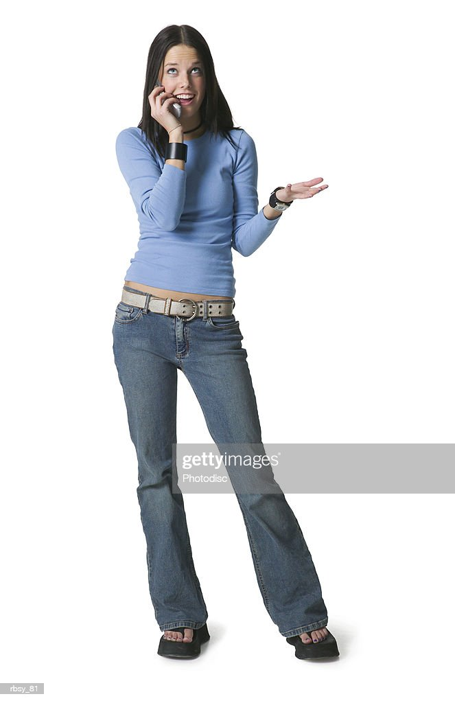 a caucasian female teenager in jeans and a blue shirt chats with a friend on a cell phone : Foto de stock