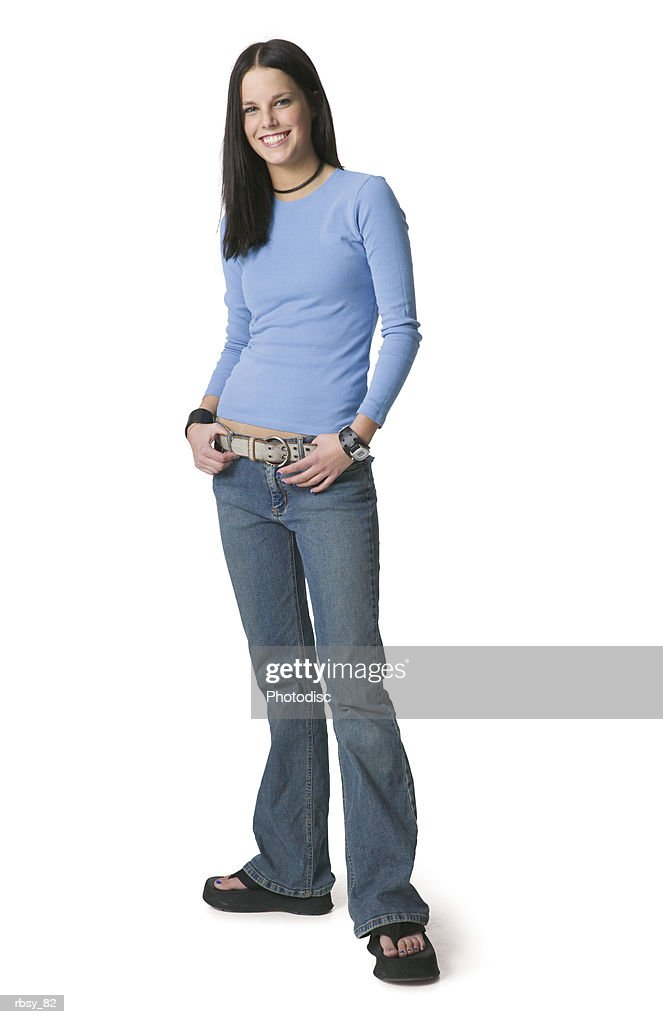 a caucasian female teenager in jeans and a blue shirt smiles into the camera : Foto de stock