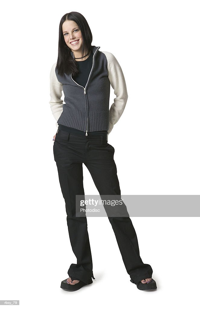 a caucasian female teenager in jeans and a tan and blue sweater puts her hands behind her back and smiles : Foto de stock