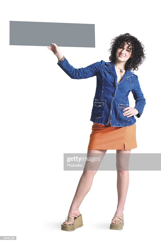 a caucasian girl with brown curly hair wearing a denim shirt and an orang skirt stands with a hand on one of her hips and her other hand holding a blank sign up to the side of her head : Stockfoto
