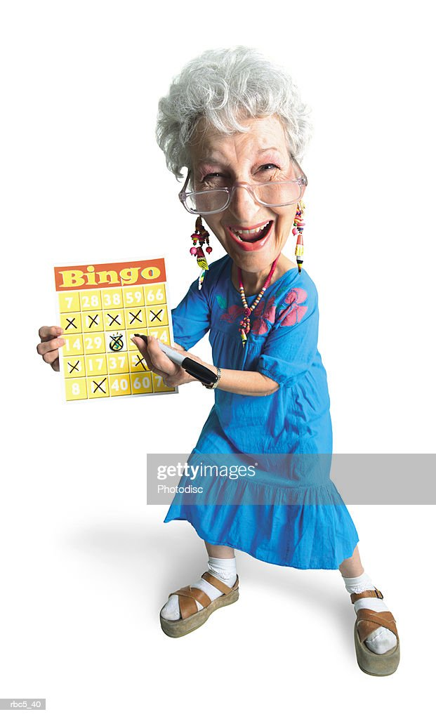 a caucasian grandma wearing glasses and a blue mu mu smiles while she holds up her bingo chart to show five x's in a row : Stockfoto
