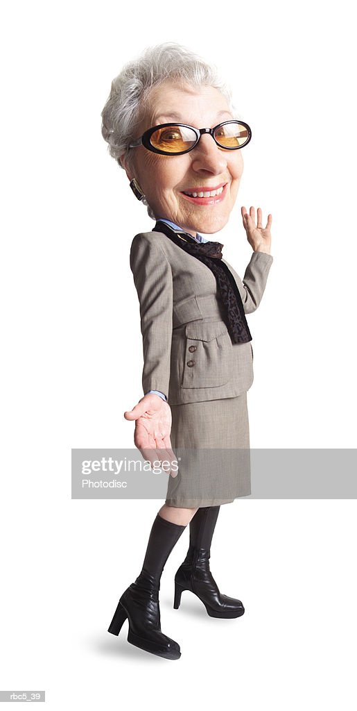 a caucasian grandma wears tinted glasses and knee high boots and a very modern looking taupe suit while smiling at the camera : Stockfoto