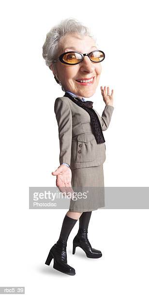 a caucasian grandma wears tinted glasses and knee high boots and a very modern looking taupe suit while smiling at the camera