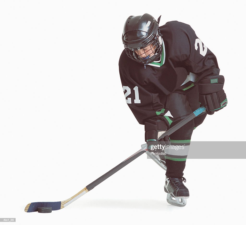 a caucasian hockey player wearing a black uniform is skating with his stick about to hit the puck : Foto de stock