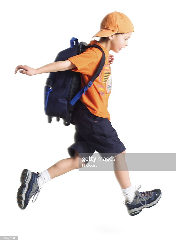 a caucasian little boy with an orange ballcap and a backpack runs along to school : Stockfoto