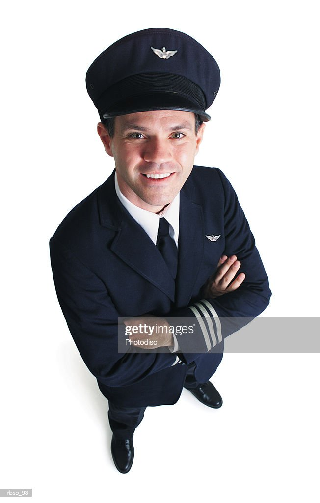 a caucasian male airline pilot in his blue uniform folds his arms and smiles as he looks up at the camera : Foto de stock