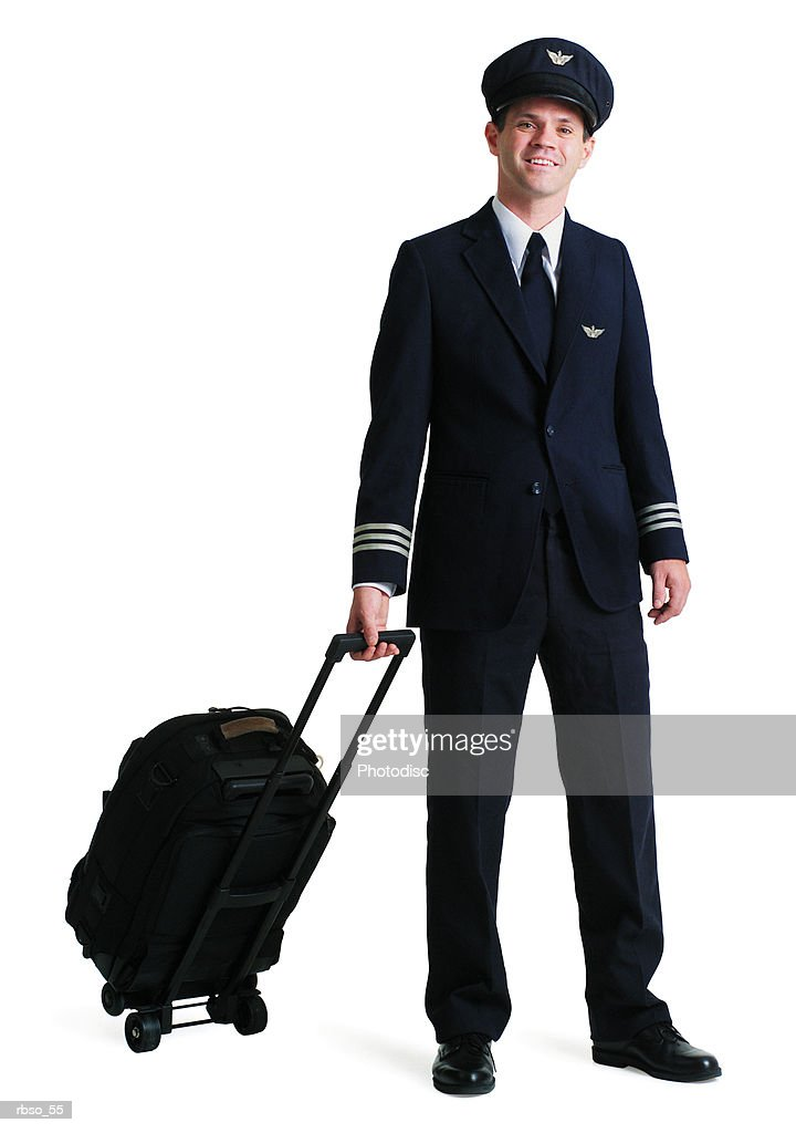 a caucasian male airline pilot smiles as he pulls his luggage : Foto de stock