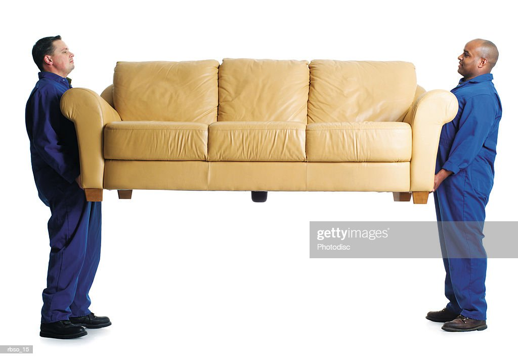 a caucasian male and an african american male mover carry a couch together : Stockfoto