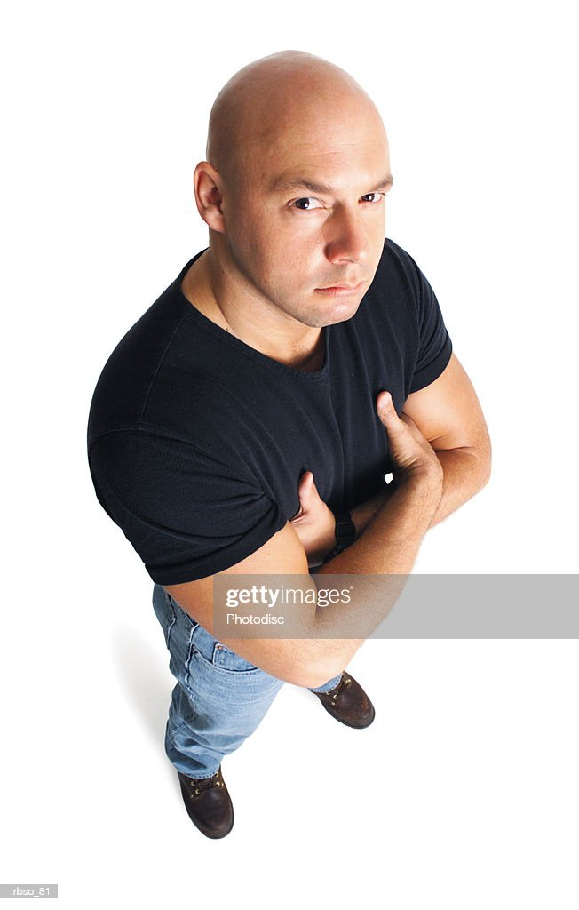 a caucasian male bouncer in a black tee shirt folds his arms and scowls up at the camera : Foto de stock