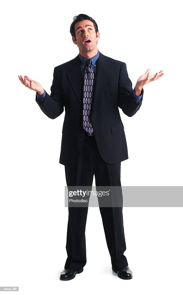 a caucasian male business man dressed in a dark suit throws up his hands in disbelief : Foto de stock
