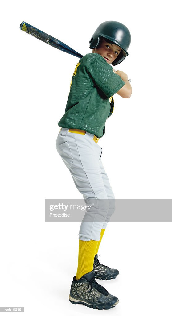 a caucasian male child dressed as a baseball player in a green uniform stands bat raised ready to swing : Stockfoto