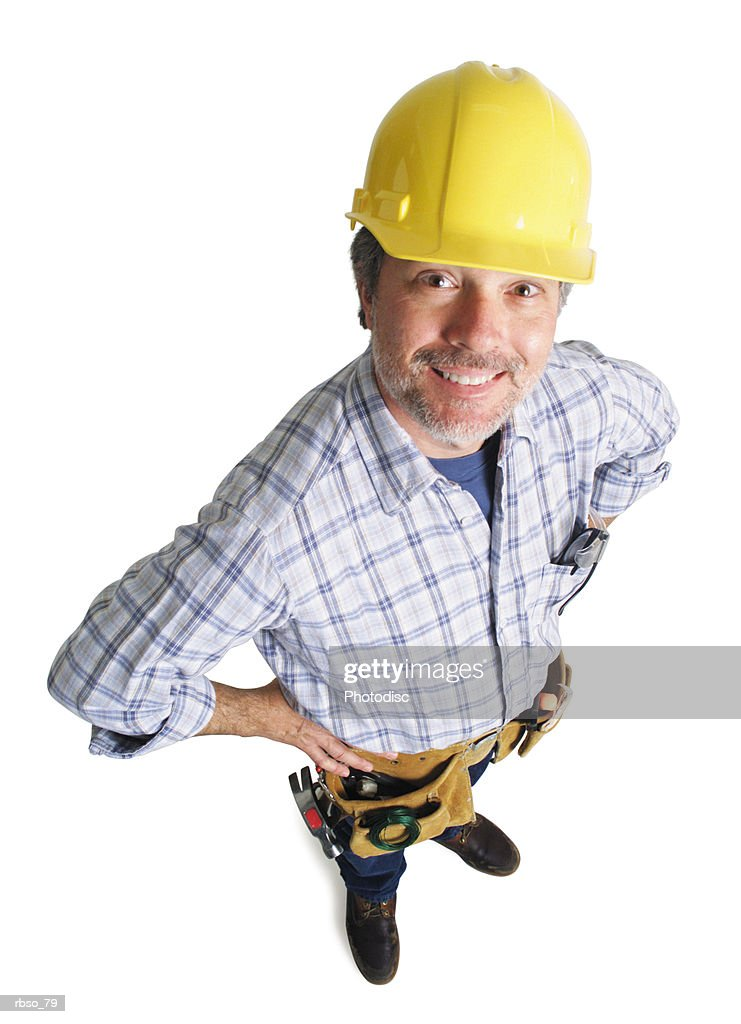 a caucasian male construction worker wearing a tool belt smiles as he looks up at the camera : Foto de stock