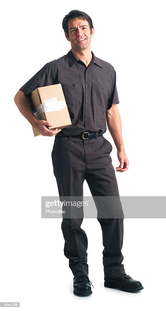 a caucasian male delivery man dressed in a brown uniform holds a package under one arm : Foto de stock