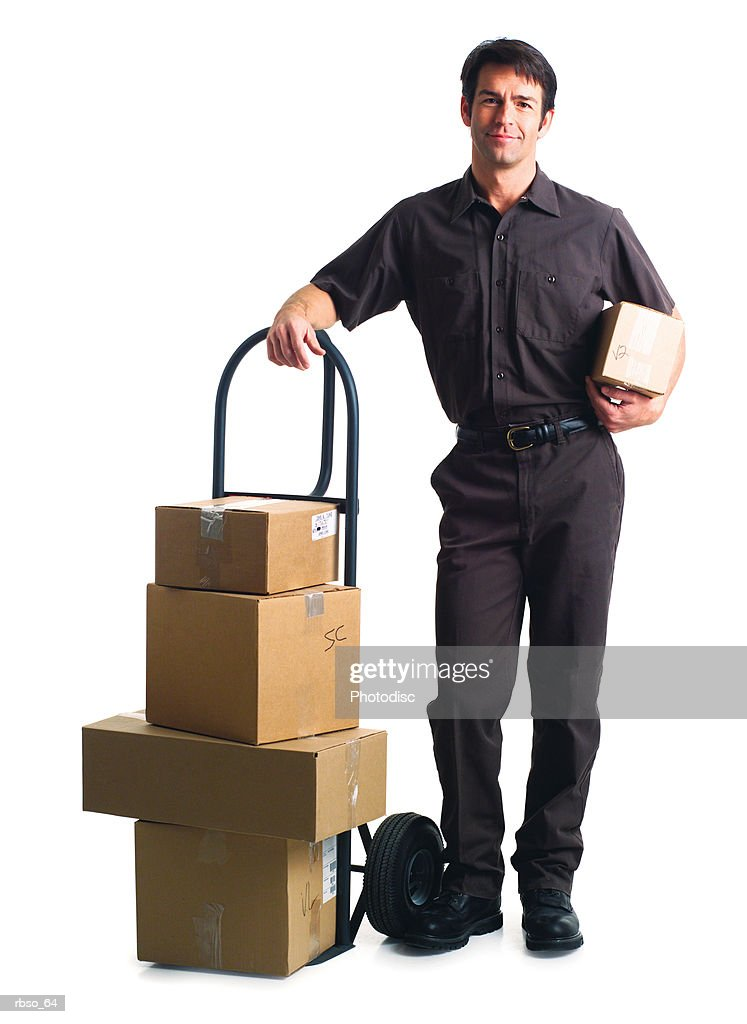 a caucasian male delivery man stands in uniform surrounded by many boxes : Foto de stock