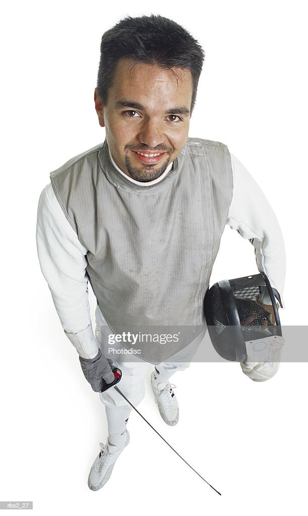 a caucasian male fencer holds his face mask and sword while he smiles and looks up at the camera : Foto de stock