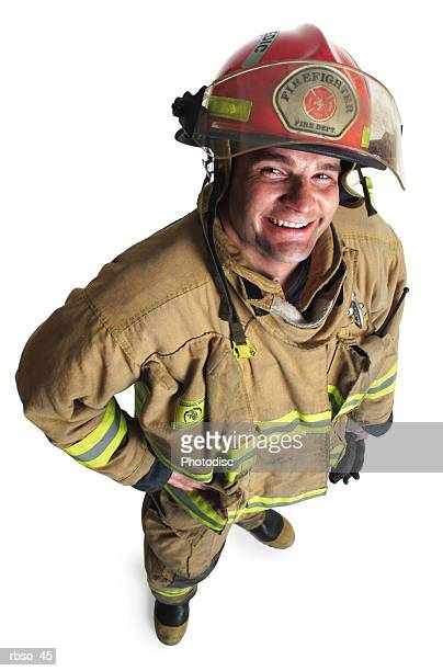 a caucasian male firefighter in his gear smiles as he looks up at the camera - fire protection suit - fotografias e filmes do acervo