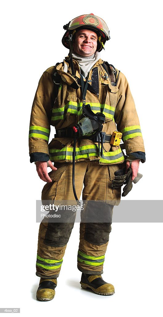 a caucasian male firefighter stands smiling in all his gear : Foto de stock