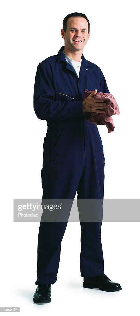 a caucasian male mechanic in a blue jumpsuit cleans his hands with an oily rag : Stockfoto