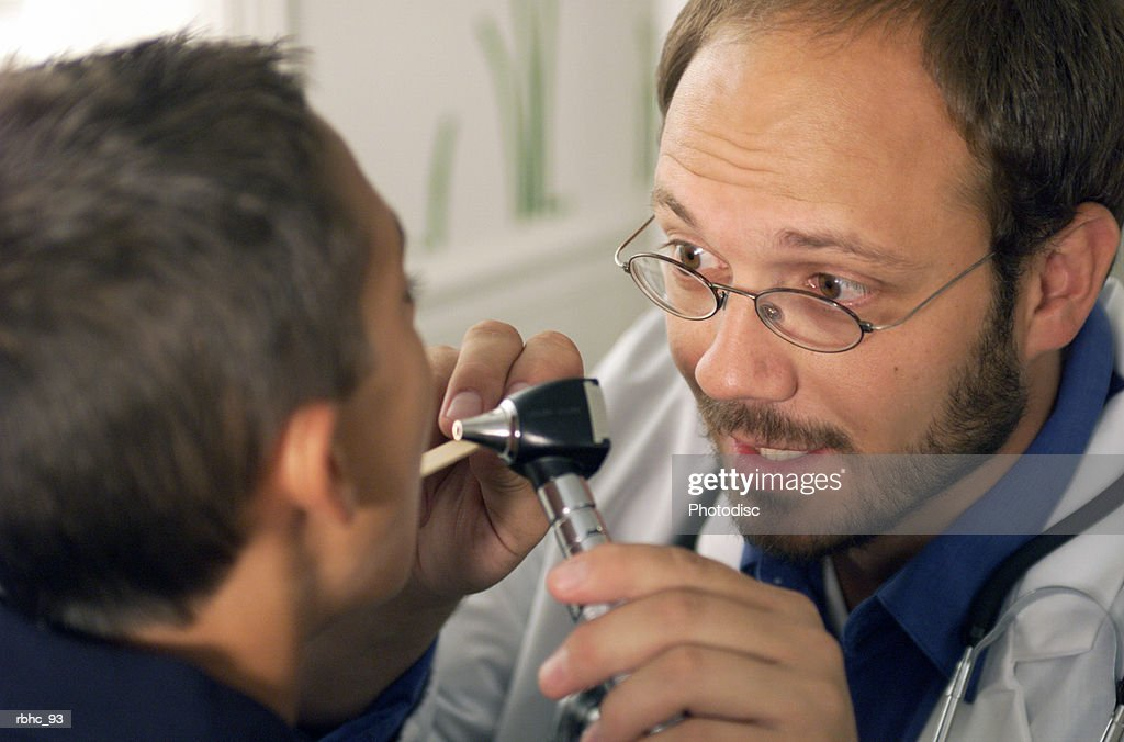 a caucasian male pediatrician with a beard checks the throat of a young boy patient : Stockfoto