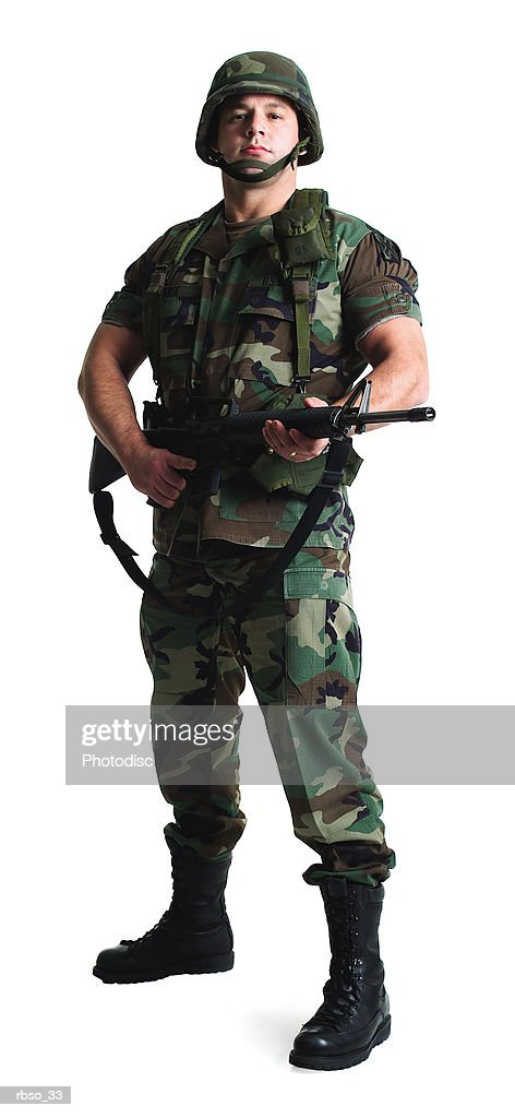 a caucasian male soldier dressed in army fatigues stands with his gun : Foto de stock